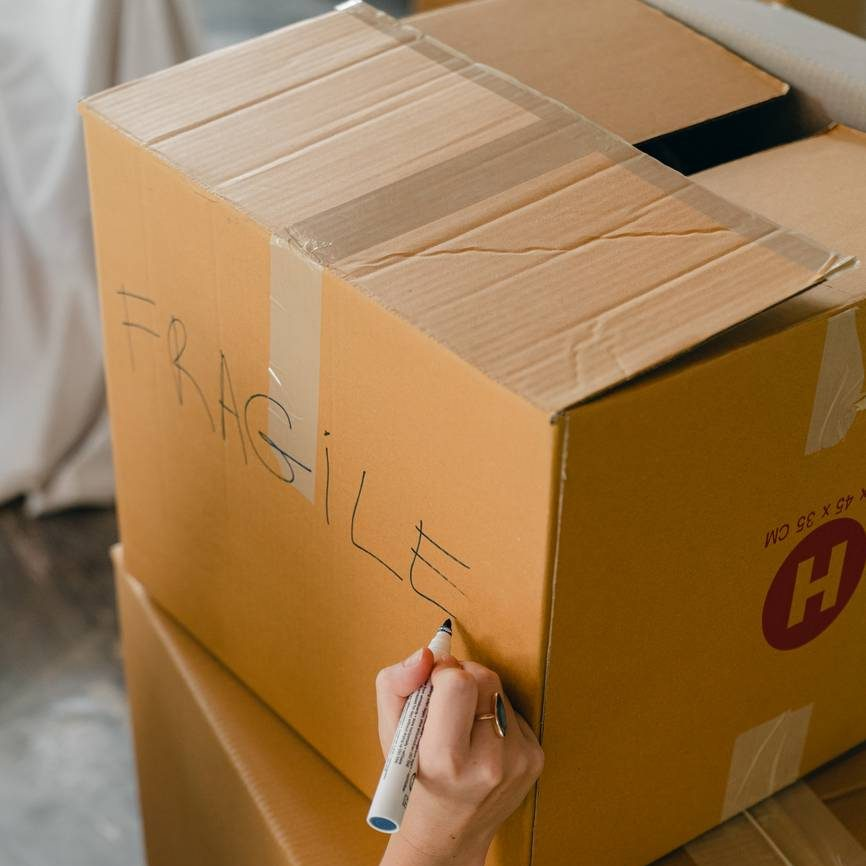 crop faceless woman sorting fragile carrying packages